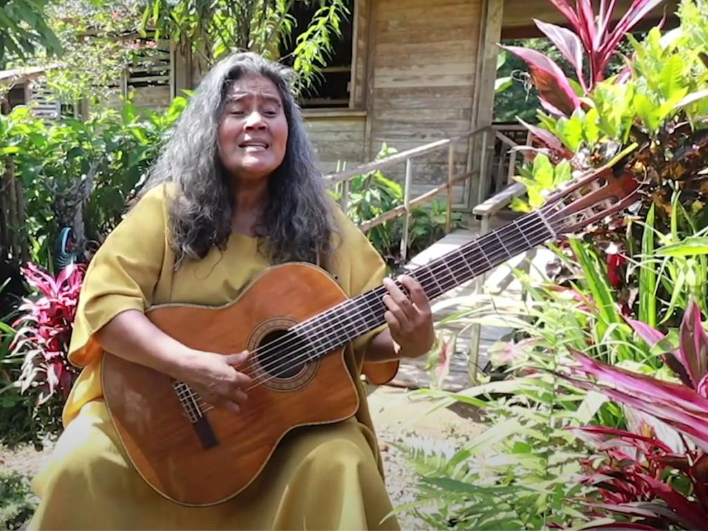 Eine Frau spielt Gitarre und singt im Regenwald