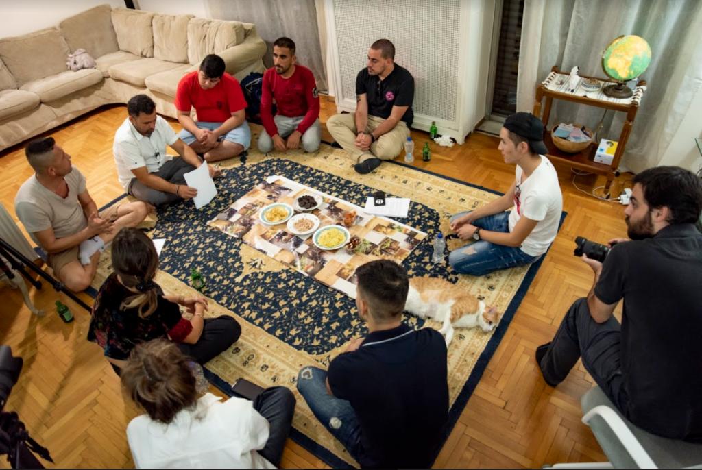 Neun Menschen sitzen im Kreis und diskutieren über einen Text