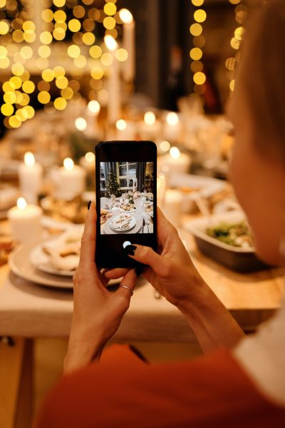 Eine Dame hält ihr Smartphone in der Hand und richtet ihre Smartphone Kamera auf einen wunderschön weihnachtlich gedeckten Tisch mit Essen, Kerzen und Lichtern.